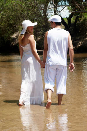 The young couple in white going on river photo