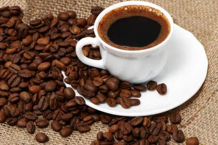cafe colombiano: Taza de café de cerca a lo largo de oscuros granos de café tostado Foto de archivo