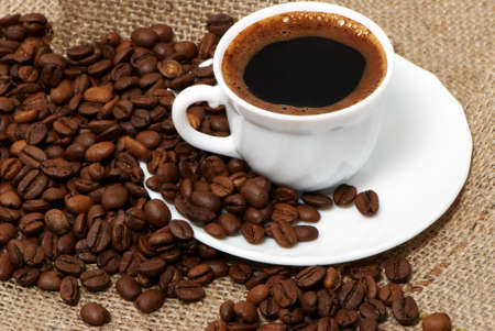 cafe colombiano: Taza de caf� de cerca a lo largo de oscuros granos de caf� tostado Foto de archivo