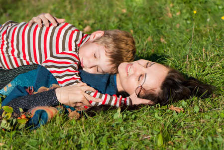 Mother and son laying on the green grass  Stock Photo