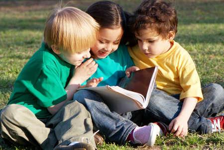 Grupa dzieci z książką na trawie w parku
