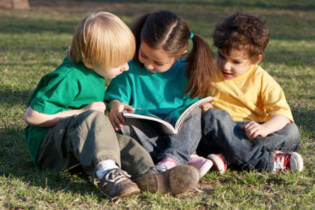 Group of children with the book on a grass in park  photo