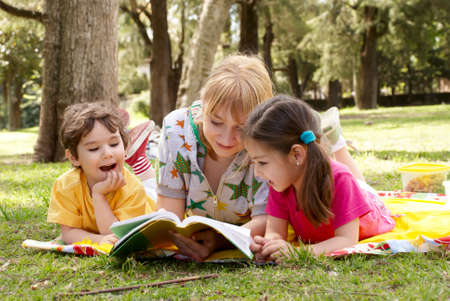 Elder sister reads to children of the book on a glade in park  Stock Photo