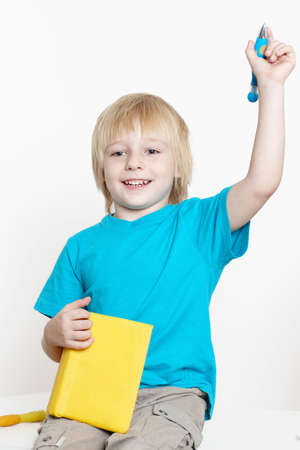 The boy of preschool age with book on a light background  photo
