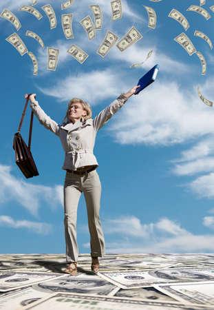 Successful business woman running in a dollar rain  Stock Photo