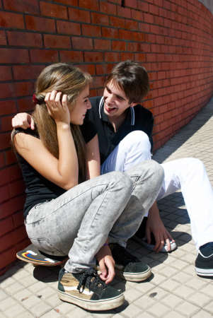 teen couple: Teenagers Sitting by a street