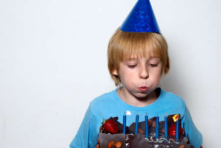 boy blowing on the candles placed in the cake photo