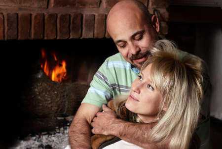 Happy pair near a fireplace in winter evening photo