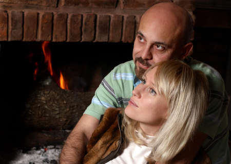 Happy pair near a fireplace in winter evening