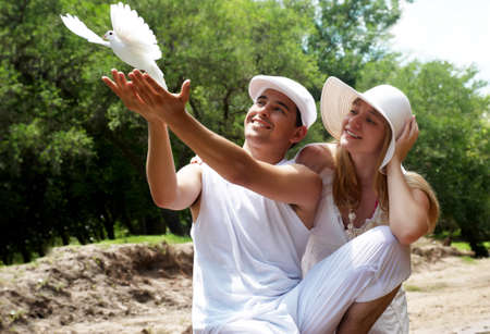woman flying: Portrait of young, happy couple with dove against the nature