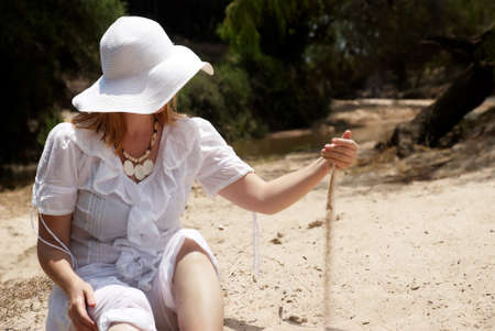 The woman in a hat playing with sand photo