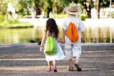 niños caminando: Pareja joven ir en la avenida en el parque Foto de archivo