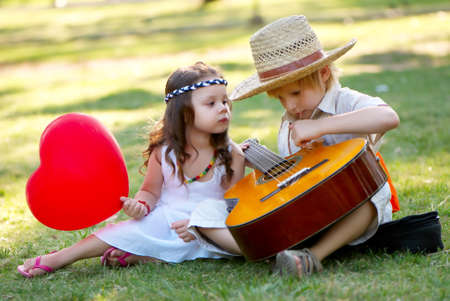 Young couple with guitar on grass in park photo