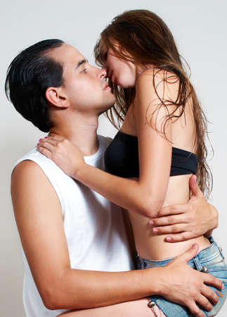 intimate young couple during foreplay on a light background photo