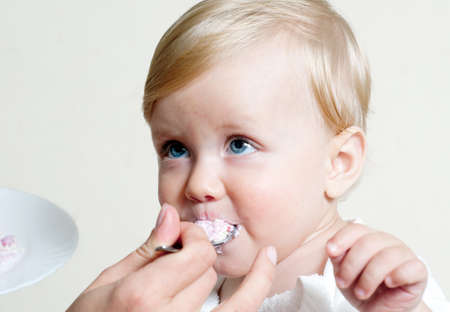 Little boy eating baby food with spoon photo