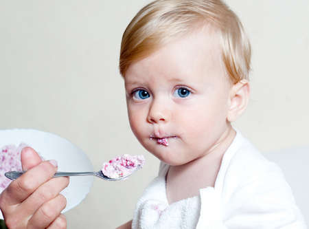 self development: Little boy eating baby food with spoon