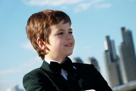 one boy only: The small gentleman against a city Stock Photo