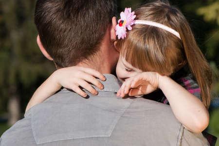 niño llorando: La pequeña niña llorando en el hombro del padre