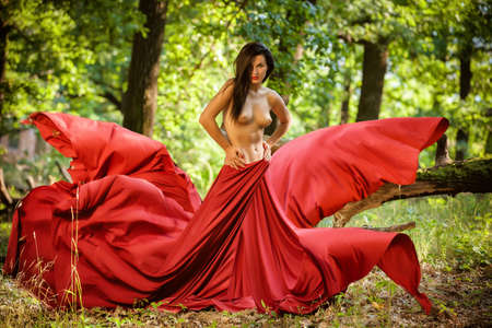 nude outdoors: Graceful nude female folded in red silk shawl outdoors Stock Photo