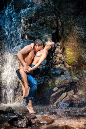 passion couple: Couple hugging and kissing under waterfall Stock Photo