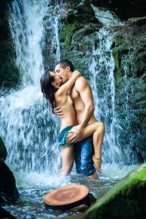 personas abrazadas: Pareja abrazándose y besándose bajo la cascada Foto de archivo
