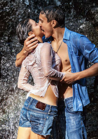 novios besandose: Pareja abraz�ndose y bes�ndose bajo la cascada Foto de archivo