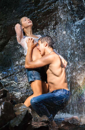 Couple hugging and kissing under waterfall Stock Photo