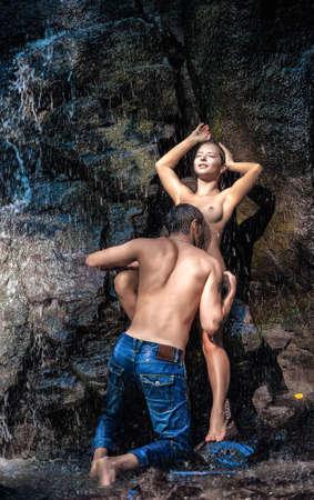 personas besandose: Pareja abrazándose y besándose bajo la cascada Foto de archivo