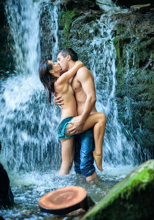 Couple hugging and kissing under waterfall photo