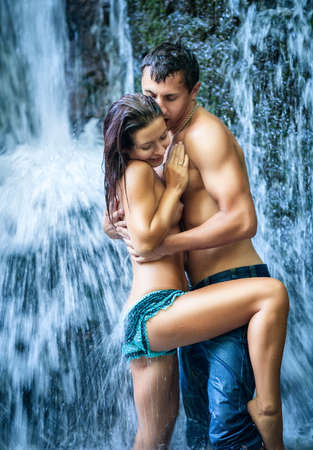 abandonment: Couple hugging and kissing under waterfall Stock Photo