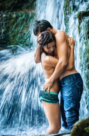 parejas romanticas: Pareja abrazándose y besándose bajo la cascada Foto de archivo
