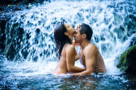 desires: Couple hugging and kissing under waterfall Stock Photo