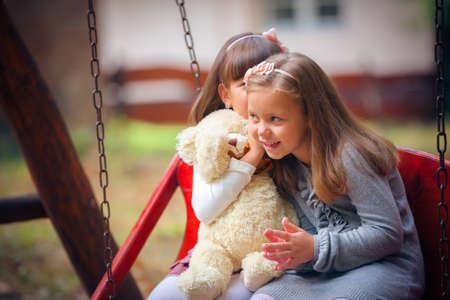 Happy little girlfriends in park photo