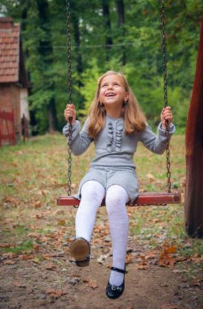 girl on swing: Happy Little Girl Smiling on Swing Stock Photo