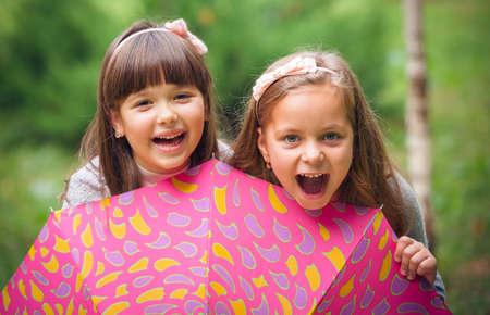 Happy little girlfriends in park