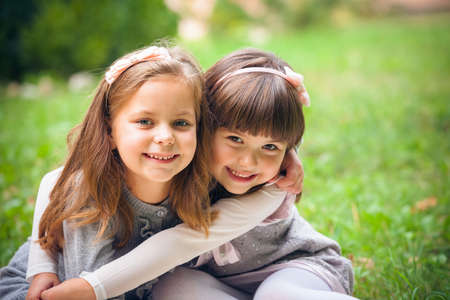 two girls hugging: Happy little girlfriends in park