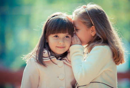 girls kissing girls: Happy little girlfriends in park