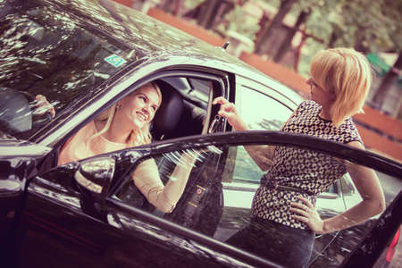 car loans: Car dealer giving keys of a new car to head customer