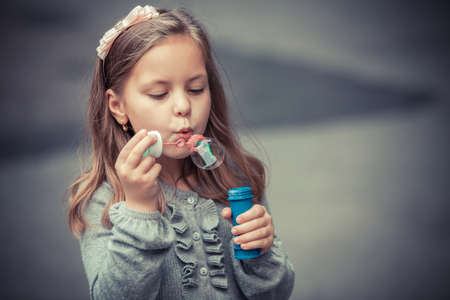 soap bubbles: Portrait of funny lovely little girl blowing soap bubble