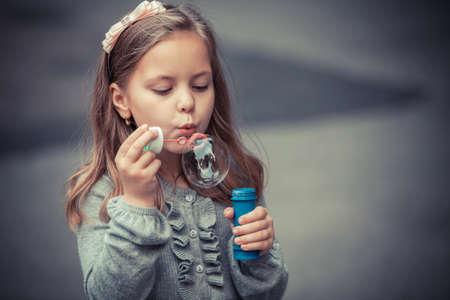 girl blowing: Portrait of funny lovely little girl blowing soap bubble