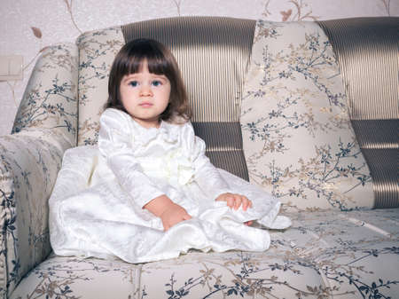 Baby dressed in white dress Stock Photo