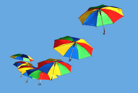 flying umbrella with on blue sky day photo