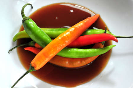 group of spicy peppers in sauce hot dish background  photo