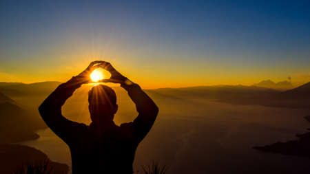 Dawn views of Lake Atitlan and hiker doing shapes from the heights of Indian Nose pointview Stock fotó