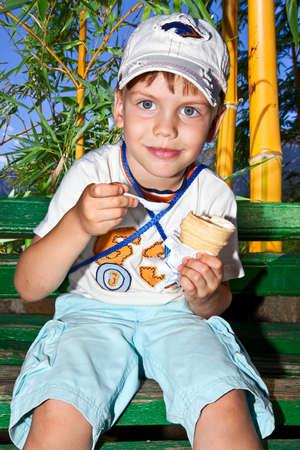 small boy kid on nature eats ice cream