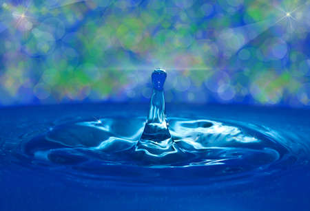 perturbing: small drop falls in blue transparent water Stock Photo