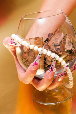 Hand with artificial nails holding glass