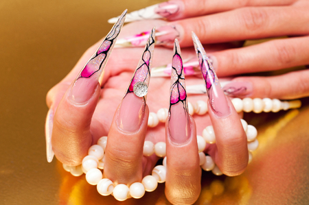 Hand with artificial nails holding pearls Stock Photo
