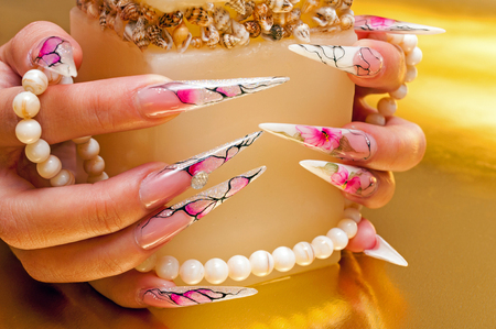 Hands with artificial nails and pearls
