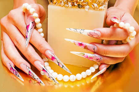 Hand with long artificial nails and pearls